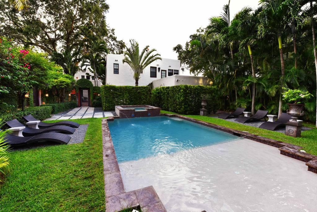 Airbnb backyard and pool with green lush grass